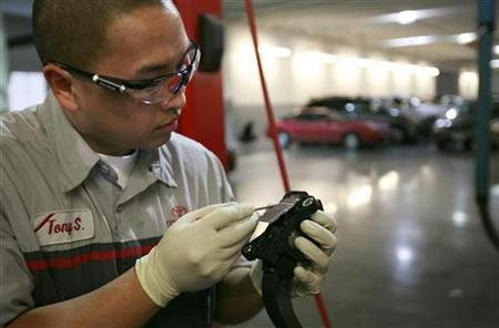 Toyota service technician Tony Saelee removes a cover from an accelerator pedal from a recalled 2010 Toyota Camry in Daly City, California, February 4, 2010. REUTERS/Robert Galbraith