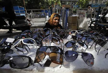 A woman sells sunglasses at a market in Tehran June 6, 2009. Islamic Republic's underlying economic problems are likely to be aggravated by any more sanctions over its disputed nuclear programme and by political unrest set off by a fiercely disputed presidential election in June. REUTERS/Ahmed Jadallah/Files