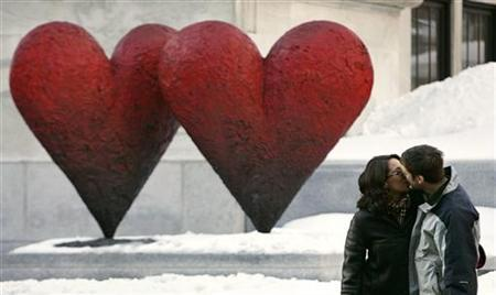 Andee Shuster and Ben Urovitch kiss as in front of a heart shaped sculpture outside the Montreal Museum of Arts, February 13, 2005.