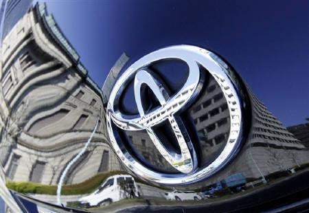 The Bank of Japan building is reflected on Toyota Motor Corp's Prius hybrid car in Tokyo February 18, 2010. REUTERS/Toru Hanai