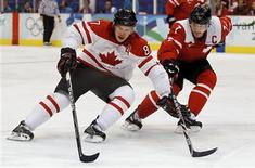 <p>Canada's Sidney Crosby (L) with a nose injury drives to the net on Switzerland's Mark Streit during their men's preliminary round ice hockey match at the Vancouver 2010 Winter Olympics February 18, 2010. REUTERS/Hans Deryk</p>