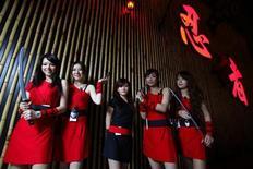 """<p>Официантки ресторана """"Ниндзя"""" позируют для групповой фотографии в Тайбэе 8 февраля 2010 года. Посетителям ресторана """"Ниндзя"""" в Тайбэе приходится нелегко - до столика они добираются через ров, а блюда заказывают официанткам, орудующим холодным оружием. REUTERS/Nicky Loh</p>"""