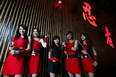 <p>Waitresses pose for a group photo outside the Ninja restaurant in Taipei February 8, 2010. REUTERS/Nicky Loh</p>