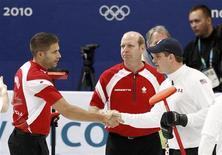 <p>United States skip John Shuster (R) shakes hands with Canada's third John Morris (L) as skip Kevin Martin looks on after Canada defeated the United States in their men's round robin curling game at the Vancouver 2010 Winter Olympics February 22, 2010. REUTERS/Andy Clark</p>