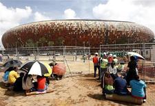 <p>Pessoas em busca de empregos temporários aguardam em frente ao Soccer City, principal estádio da Copa do Mundo de 2010 na África do Sul. O estádio estará pronto para os primeiros eventos de teste em abril ou maio. 17/02/2010 REUTERS/Siphiwe Sibeko</p>