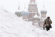 <p>A woman walks in the Red Square under heavy snowfall with St.Basil's Cathedral in the background in central Moscow February 21, 2010. REUTERS/Denis Sinyakov</p>