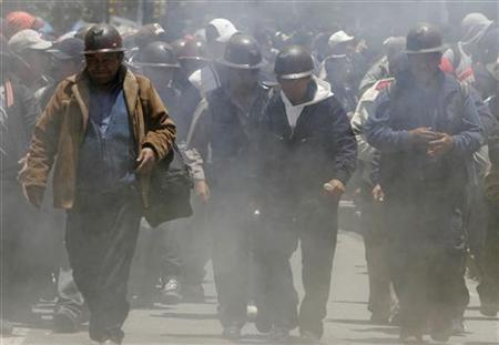 Independent miners march amid smoke from dynamites they threw during a rally in the centre of La Paz February 6, 2007. REUTERS/David Mercado