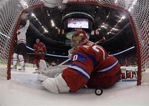 <p>Нападающий сборной Канады Райан Гетцлаф (слева) забрасывает шайбу в ворота голкипера сборной России Евгения Набокова в матче 1/4 финала Олимпийских игр в Ванкувере 24 февраля 2010 года. Сборная России по хоккею в четверг потерпела поражение от команды Канады в четвертьфинале олимпийского турнира в канадском Ванкувере со счетом 3:7. REUTERS/Julie Jacobson/Pool</p>