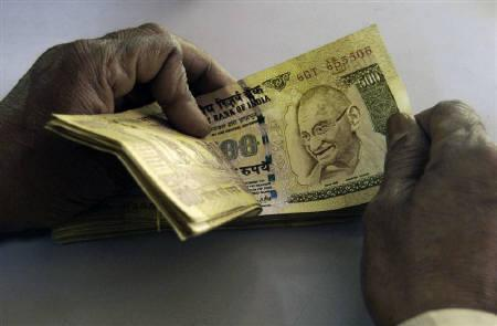 A bank employee counts currency notes at a cash counter inside a bank in Agartala February 26, 2010.  REUTERS/Jayanta Dey