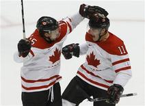 <p>Patrick Marleau (11) of Canada celebrates his goal against Slovakia with Dany Heatley (15) in their mens's play-offs semifinals hockey game at the Vancouver 2010 Winter Olympics February 26, 2010. REUTERS/Todd Korol</p>