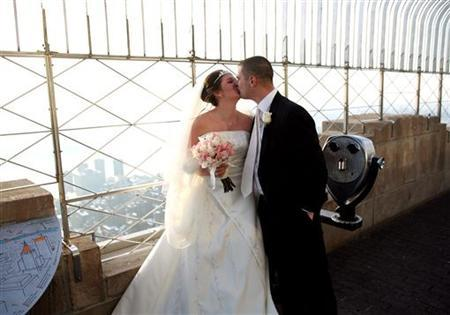 Newlyweds kiss after getting married atop the Empire State Building in New York February 14, 2006. REUTERS/Jeff Zelevansky