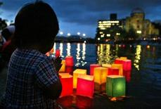 <p>A young girl folds her hands in prayer as Japanese paper lanterns are floated down Motoyasu River, near ground zero, for the atomic bomb victims of Hiroshima August 6, 2002. HREUTERS/Eriko Sugita</p>