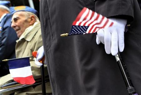 A U.S. Armed Services veteran holds an American and a French flag during the Veterans Day parade in New York, November 11, 2009 (Photo: © Shannon Stapleton / Reuters)
