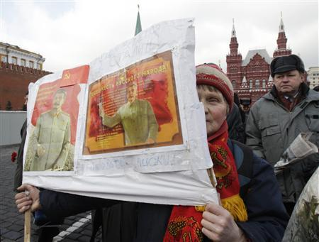 A woman, holding portraits of Soviet dictator Josef Stalin, walks along the Red Square to attend a wreath laying ceremony at the tomb of Stalin marking the anniversary of his death at the Kremlin wall in Moscow March 5, 2010. REUTERS/Sergei Karpukhin