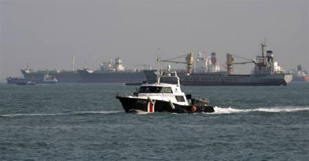 A Police Coast Guard vessel patrols the shipping lanes near freight ships off the coast of Singapore March 4, 2010. REUTERS/Vivek Prakash