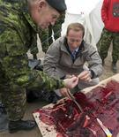 <p>Canadian Minister of Defence Peter MacKay gives a piece of seal meat to the Chief of Defence Staff General W.J. Natynczyk (L) during a community event in Iqaluit, Nunavut in the Canadian Arctic August 22, 2009 file photo. REUTERS/Andy Clark</p>