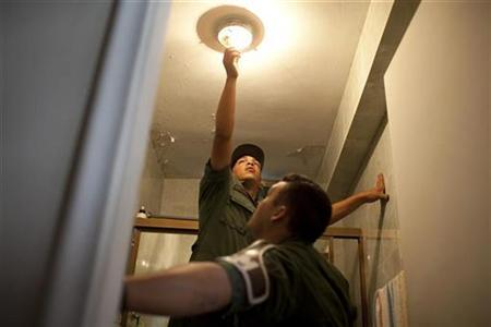 Venezuelan soldiers replace incandescent light bulbs with energy saving bulbs in a house in Caracas March 8, 2010. REUTERS/Carlos Garcia Rawlins