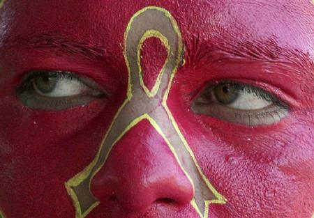 A social activist displays an anti-AIDS symbol on his face during an awareness campaign in Chandigarh February 14, 2010. REUTERS/Ajay Verma/Files