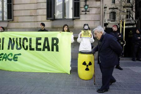 A man walks in front of Greenpeace activists protesting against nuclear waste disposal and asking for the closure of all nuclear power plants in Spain, in Barcelona March 4, 2010.  REUTERS/Gustau Nacarino