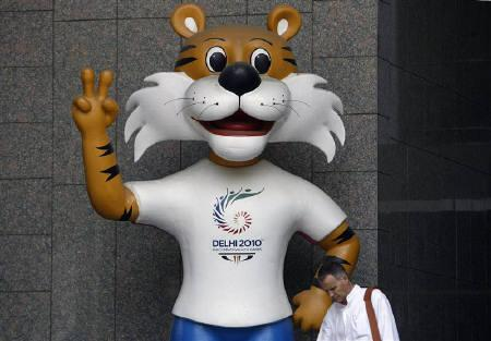 A commuter walks past the New Delhi Commonwealth Games 2010 mascot in New Delhi October 3, 2009. The government has compiled a list of do's and don'ts for its citzens at this year's Commonwealth Games to help showcase New Delhi's charms.  REUTERS/Parth Sanyal/Files