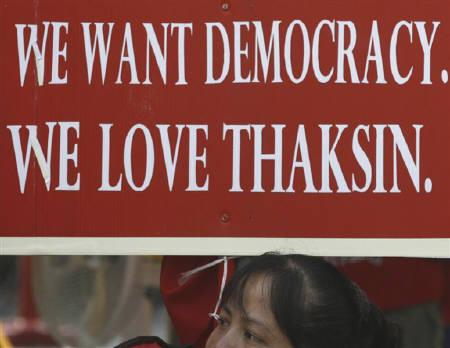 A supporter of former premier Thaksin Shinawatra is pictured below a sign during a rally in Bangkok March 19, 2010. A week-long rally by red-shirted anti-government protesters has delayed Thailand's signing of an accord for East Asian countries to cooperate in fending off future attacks on their currencies. REUTERS/Kerek Wongsa