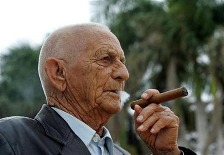 Cuban tobacco grower Alejandro Robaina, considered one of the best tobacco producers in the world, smokes one of his own brand during an interview with Reuters, at his farm in Pinar del Rio February 28, 2006. REUTERS/STR New