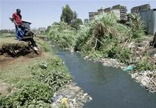 <p>Slum dwellers sit beside a river of sewage in the sprawling Mathare slums in the outskirts of the capital Nairobi March 21, 2009. REUTERS/Antony Njuguna</p>