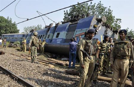 Police and railway officials stand next to an overturned coach of a passenger train which was derailed after suspected Maoist rebels blew up a railway track near Manoharpur, in  Jharkhand November 20, 2009.  REUTERS/Rajesh Kumar Sen/Files
