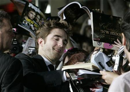 Actor Robert Pattinson, star of the new film ''The Twilight Saga: New Moon'' signs autographs for fans at the film's Los Angeles premiere November 16, 2009. REUTERS/Fred Prouser
