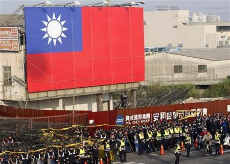 Policemen stand guard in front of a Taiwan flag outside the venue of the Taiwan and China cross strait meetings in Taichung December 21, 2009. REUTERS/Pichi Chuang