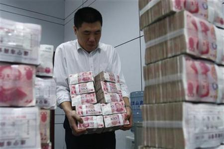 An employee carries yuan banknotes at a bank in Suining, Sichuan province, March 22, 2010. REUTERS/Stringer