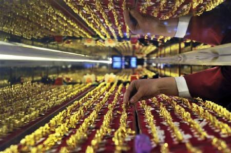 A vendor arranges gold rings on display at a jewelry shop in Shenyang, Liaoning province March 9, 2010. REUTERS/Sheng Li/Files