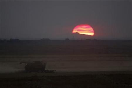The sun sets behind the Canadian Rocky Mountains as wheat farmer Glenn Sawyer harvests his crop of wheat near Acme, Alberta, September 23, 2009. REUTERS/Todd Korol