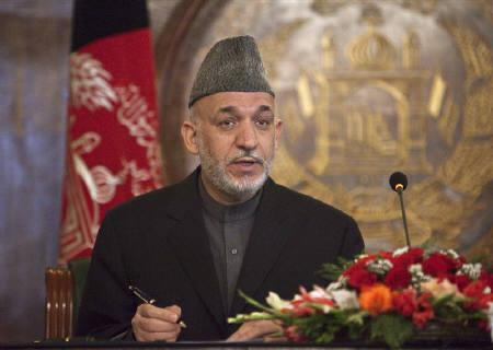 A file photo of Afghanistan's President Hamid Karzai as he signs a decree giving more authority to an anti-graft body in Kabul March 18, 2010. REUTERS/Ahmad Masood/Files