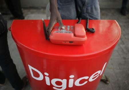 A man uses a Digicel wireless phone in downtown Port-au-Prince March 22, 2010. Earthquake-stricken Haiti's telecoms market could double in size in five years if a donor-backed reconstruction effort successfully multiplies jobs and wealth, an executive of the nation's largest mobile phone operator said on March 30, 2010. REUTERS/Eduardo Munoz