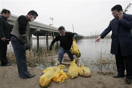 An officer from the local health bureau carries dead babies found dumped in a river on the outskirts of Jining, Shandong province, March 30, 2010. REUTERS/Stringer