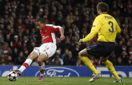 Arsenal's Theo Walcott scores past Barcelona's Gerard Pique during their Champions League quarter-finals first leg soccer match at Emirates stadium in London March 31, 2010.   REUTERS/Eddie Keogh