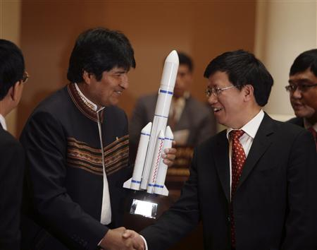 Bolivia's President Evo Morales (L) shakes hands with Wu Yanhua, a representative of the China Aerospace Science and Technology Corporation, as he holds a miniature model of the ''Tupak Katari'' communications satellite in La Paz April 1, 2010. REUTERS/Gaston Brito