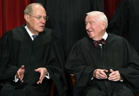 Supreme Court Justice Anthony M. Kennedy (L) speaks with Justice John Paul Stevens during their official photograph with the other Justices at the Supreme Court in Washington September 29, 2009. REUTERS/Jim Young
