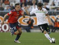 <p>David Villa do Valencia (dir) e Javier Camuna do Osasuna disputam jogada. David Villa marcou duas vezes nos últimos cinco minutos e manteve o Valencia na zona de classificação para a Liga dos Campeões com um 3 x 0 no domingo. 04/04/2010 REUTERS/Heino Kalis</p>