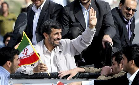 EDITORS' NOTE: Reuters and other foreign media are subject to Iranian restrictions on leaving the office to report, film or take pictures in Tehran. Iran's President Mahmoud Ahmadinejad (C) holds a flag as he waves to his supporters during his provincial trip to Orumieh, 946 km (591 miles) north west of Tehran, April 7, 2010. REUTERS/President.ir/Handout