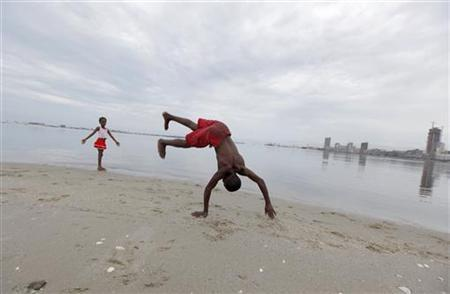 Angolan youths play against the backdrop of the capital Luanda January 20, 2010. REUTERS/Mike Hutchings