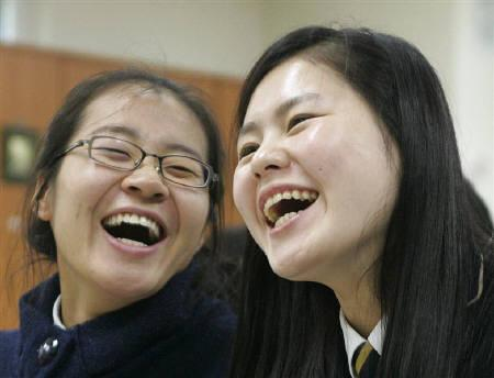 High school students, who are North Korean defectors, smile as they take part in a Korean language class at the Hangyeore middle and high school in Anseong, about 80 km (50 miles) south of Seoul, November 21, 2008. REUTERS/Jo Yong-Hak