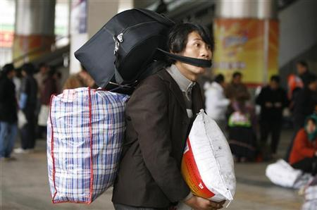 A passenger carries his belongings at a railway station in Kunming, Yunnan province January 12, 2009. REUTERS/Stringer