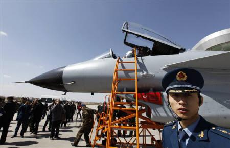 A People's Liberation Army Air Force officer looks on next to a Jian-10 fighter jet at Yangcun Air Force base, during a media trip to the 24th Air Force Division, on the outskirts of Tianjin municipality April 13, 2010 REUTERS/Petar Kujundzic