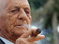 <p>Cuban tobacco grower Alejandro Robaina, considered one of the best tobacco producers in the world, smokes one of his own brands during an interview with Reuters at his farm in Pinar del Rio February 28, 2006. REUTERS/STR New</p>