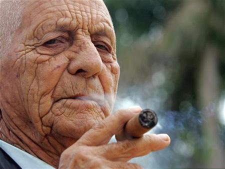 Cuban tobacco grower Alejandro Robaina, considered one of the best tobacco producers in the world, smokes one of his own brands during an interview with Reuters at his farm in Pinar del Rio February 28, 2006. REUTERS/STR New