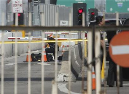 A border patrol agent (L) kneels next to the body of a man lying in one lane on the U.S. side of the U.S.-Mexico border in San Ysidro April 17, 2010. REUTERS/Jorge Duenes