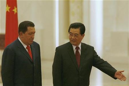 China's President Hu Jintao (R) gestures to his Venezuelan counterpart Hugo Chavez to review an honour guard during a welcome ceremony at the Great Hall of the People in Beijing September 24, 2008. REUTERS/Alfred Cheng Jin