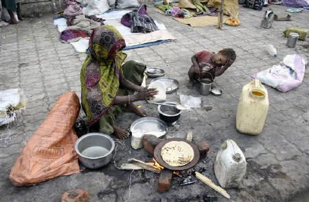 A homeless woman prepares bread on a footpath as a child looks on in  Ahmedabad in this February 26, 2010 file photo. REUTERS/Amit Dave/Files